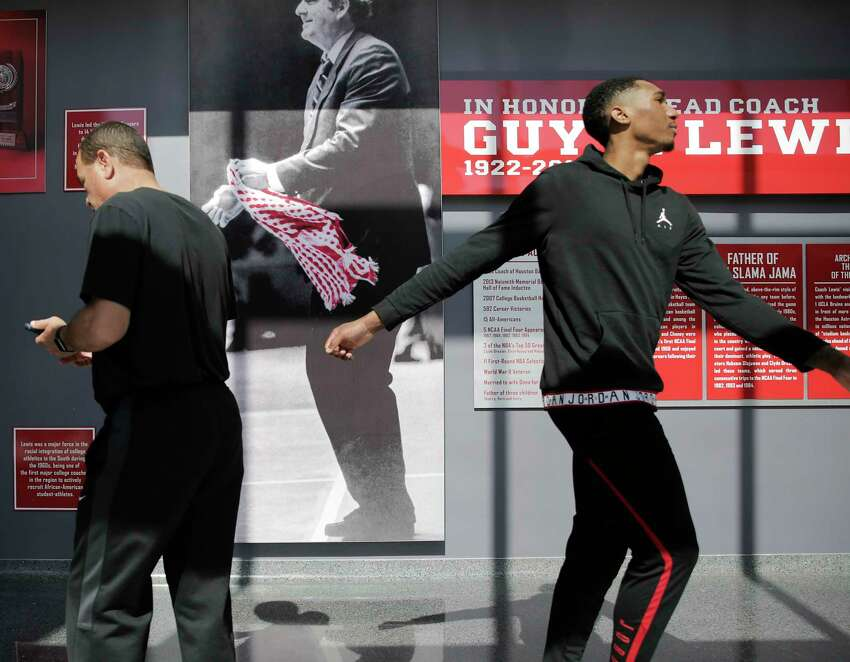 UH guard Armoni Brooks and head coach Kelvin Sampson walk past a photo of Guy V. Lewis after talking to the media at the before loading onto a bus to leave for the NCAA tournament in Tulsa on Wednesday, March 20, 2019.