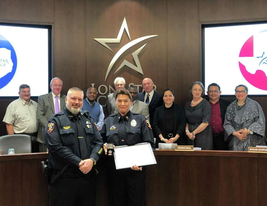 Lone Star College Police Captain Sandra Joachim (front center) poses for a photo with LSC Police Chief Paul Willingham (front left) after receiving the LSC Police Medal of Valor during the LSC board of trustees meeting in March 2019. LSC Chancellor Stephen C Head and LSC trustees stand behind the officers. Photo: Courtesy Of Lone Star College