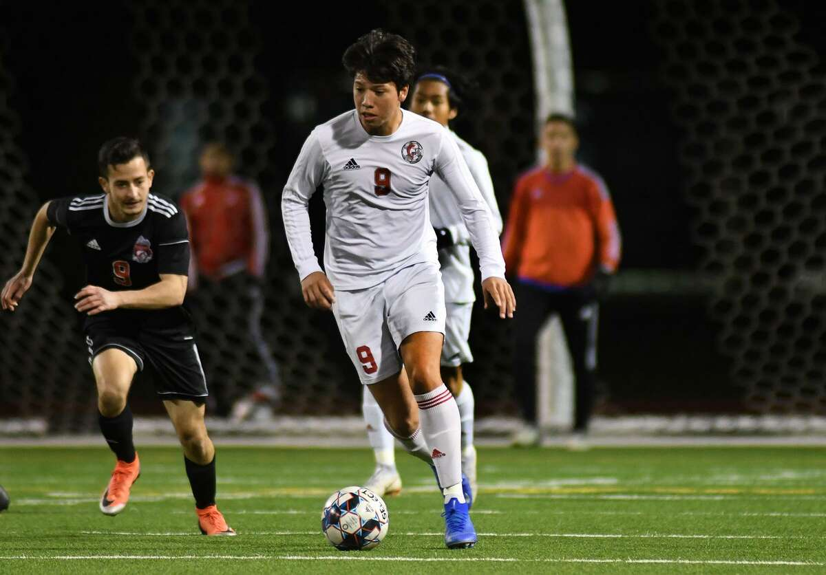 Cy Lakes sophomore Ulysses Jaimes (9) pushes the ball upfield ahead of Langham Creek senior forward Emanuel Morales, left, late in the 2nd period of their District 14-6A matchup at LCHS on Match 15, 2019.