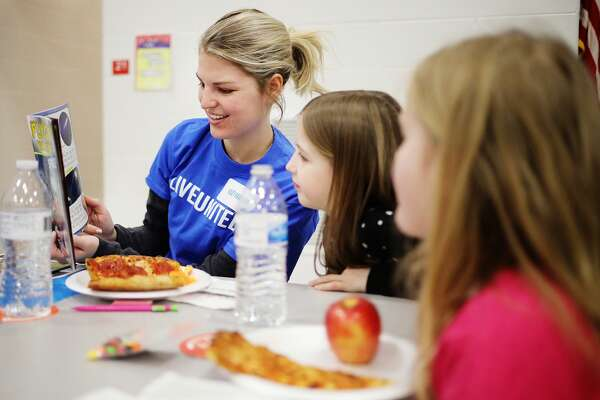 Kasey Harter, left, a volunteer with United Way of Midland County's Young Leaders United group, reads a book with Plymouth Elementary second graders Vivienne Jacobscarter, 8, center, and Cayla Oliver, 7, right, during a celebration of March being National Reading Month on Thursday, March 21, 2019 at the school. (Katy Kildee/kkildee@mdn.net)