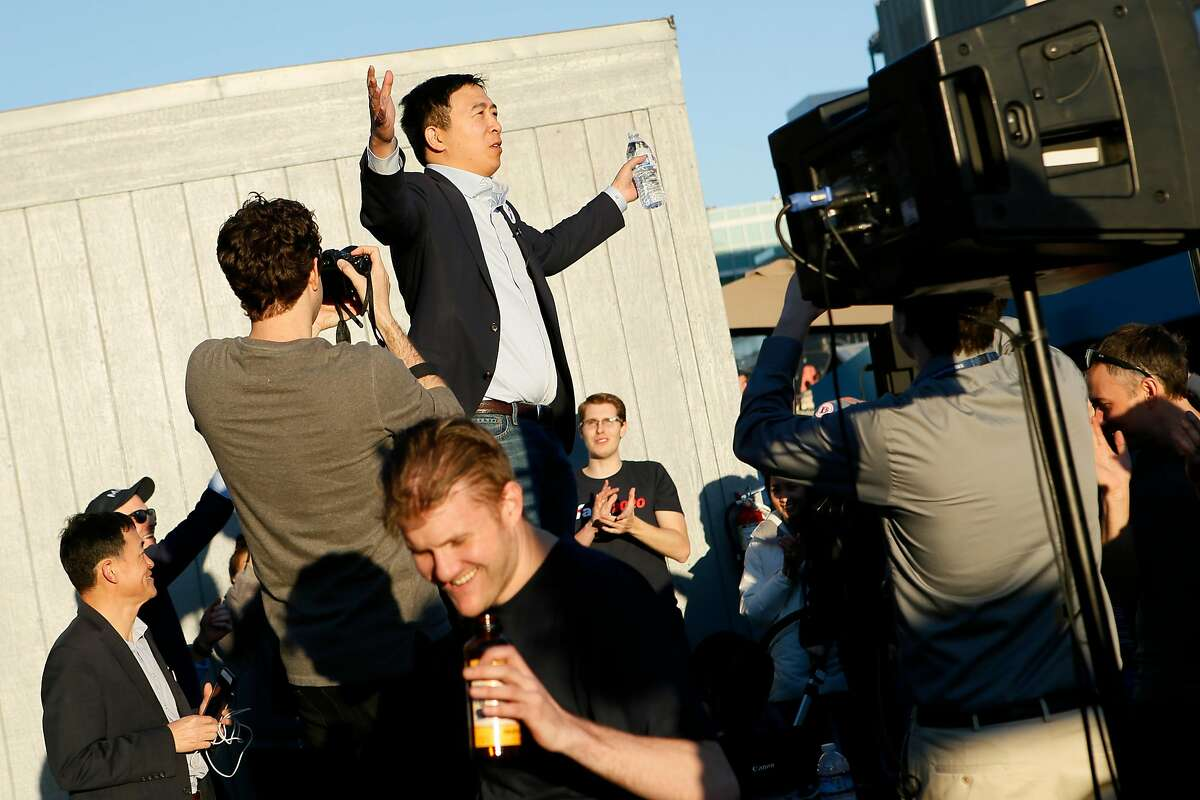 Presidential candidate Andrew Yang stands up on the table to acknowledge the roaring crowd of supporters during his campaign rally at SPARK Social SF on Friday, March 15, 2019, in San Francisco, Calif.