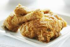 Plate of crispy fried chicken on a white background. More fried chicken below...