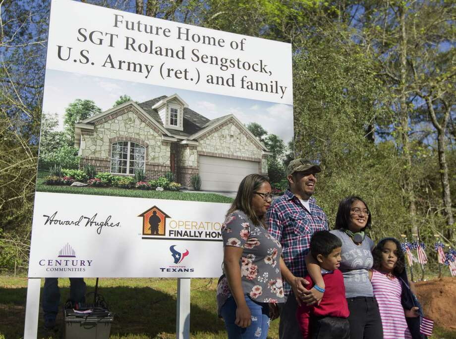 U.S. Army Sgt. Roland Sengstock shares a laugh as he and his family pose for the photo in front of an artist rendering of the future home his family recieved as part of Operation Finally Home, which provides mortgage-free homes for veterans, Thursday, March 21, 2019, in Willis. Photo: Jason Fochtman, Houston Chronicle / Staff Photographer / © 2019 Houston Chronicle