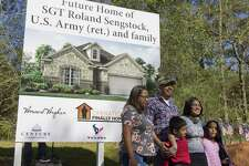 U.S. Army Sgt. Roland Sengstock shares a laugh as he and his family pose for the photo in front of an artist rendering of the future home his family recieved as part of Operation Finally Home, which provides mortgage-free homes for veterans, Thursday, March 21, 2019, in Willis.