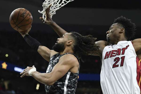Patty Mills scores on a reverse layup as Hassan Whiteside (21) of the Miami Heat defends during NBA action in the AT&T Center on Wednesday, March 20, 2019.