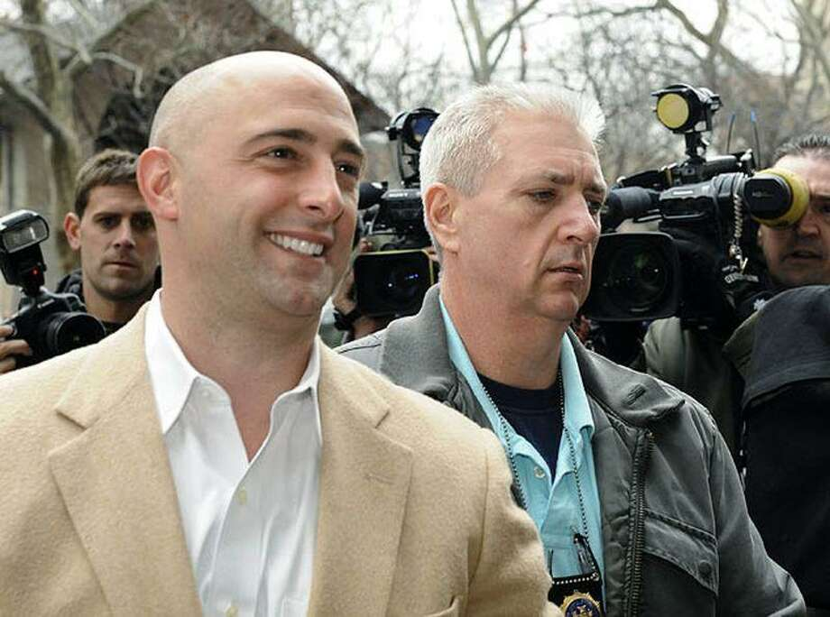 David Loglisci of the Rowayton section of Norwalk, left, former chief investment officer for New York Comptroller Alan Hevesi, is escorted in handcuffs into Manhattan criminal court in New York. He was indicted on charges he took kickbacks and other payments to steer millions of dollars in state pension fund investments to favored companies, state officials said. Photo: LOUIS LANZANO /AP