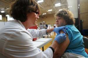 Milford Health Department dental hygienist Elaine Colangelo gets her annual flu shot from nurse Linda Bespuda, RN, at the Wellness Works! Health Fair at the Parsons Gymnasium in Milford, Conn. on Thursday, October 25, 2018. The Milford Health Department at 82 New Haven Avenue gives flu shots on the second Tuesday of every month from 2:30 to 4 p.m.