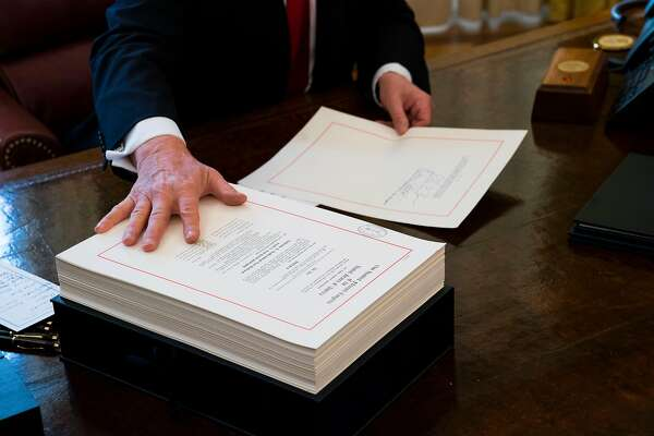 FILE -- President Donald Trump with the tax bill at a signing ceremony at the White House in Washington, Dec. 22, 2017. Polling shows those getting smaller refunds are less likely to view the tax overhaul favorably, even if their take-home pay grew. (Doug Mills/The New York Times)