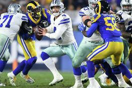 Dallas Cowboys quarterback Dak Prescott (4) tries to escapes the Los Angeles Rams defense during the NFL Divisional Round at the Los Angeles Memorial Coliseum on Saturday, Jan. 12, 2019. The Rams advanced, 30-22.