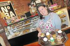 Carrie Carella, owner of NoRA Cupcake Co., 700 Main St., Middletown, displays a few customer favorites, such as the Irish Car Bomb, Adult Twinkie and Funky Monkey. Earlier this month, she opened a location in downtown New London.
