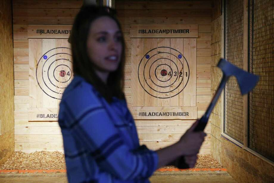 Communications director Jessie Poole demonstrates how to throw an axe at the new axe throwing range opening in Capitol Hill this week, Blade and Timber. The Broadway spot will have throwing lanes available for public and private rental and will eventually serve food and drinks. Photo: Genna Martin / seattlepi.com