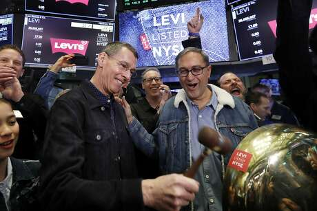Levi Strauss CEO Chip Bergh, left, is joined by CFO Harmit Singh as he rings a ceremonial bell when his company's IPO begins trading on the floor of the New York Stock Exchange, Thursday, March 21, 2019. Levi Strauss & Co., which gave America its first pair of blue jeans, is going public for the second time. The 166-year-old company, which owns the Dockers and Denizen brands, previously went public in 1971, but the namesake founder's descendants took it private again in 1985. (AP Photo/Richard Drew)