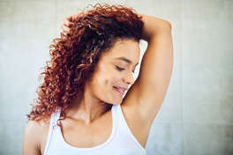 Stock image of a woman smelling her armpit.