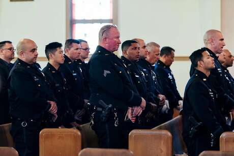 Oakland Police Officers stand during a 10 year anniversary memorial service held for 4 Oakland police officers killed in the line of duty at St Benedict's Church in Oakland, Calif., on Thursday, March 21, 2019.