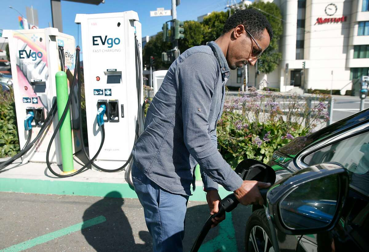 Uber driver Aradom Asfha plugs in his Chevrolet Bolt electric vehicle to a recharging station at Columbus and Bay streets in San Francisco, Calif. on Thursday, March 21, 2019.