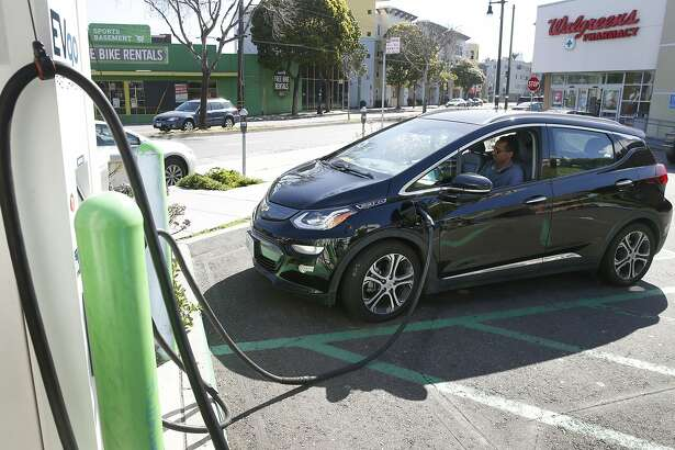 Uber driver Aradom Asfha waits in his Chevrolet Bolt electric vehicle while it's plugged into a recharging station at Columbus and Bay streets in San Francisco, Calif. on Thursday, March 21, 2019.