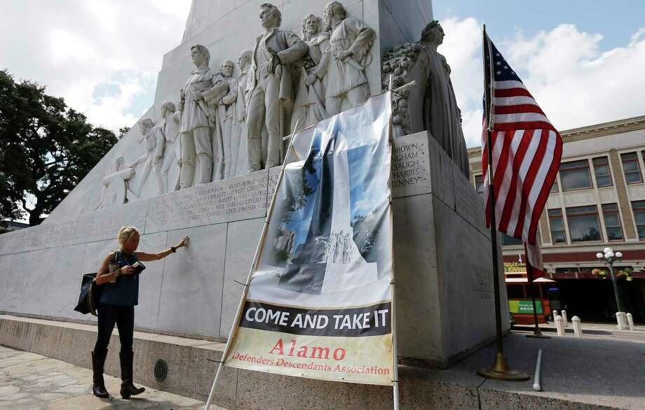 Maureen Anderson prays — with Bible in hand — beside the Cenotaph in Alamo Plaza after a rally to keep the monument in place, Oct. 14, 2017. A reader says there is no way a majority of San Antonio residents agree with the new Alamo plan. Photo: Kin Man Hui /San Antonio Express-News / ©2017 San Antonio Express-News