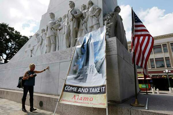 Maureen Anderson prays - with Bible in hand - beside the Cenotaph in Alamo Plaza after a rally to keep the monument in place, Oct. 14, 2017. A reader says there is no way a majority of San Antonio residents agree with the new Alamo plan.