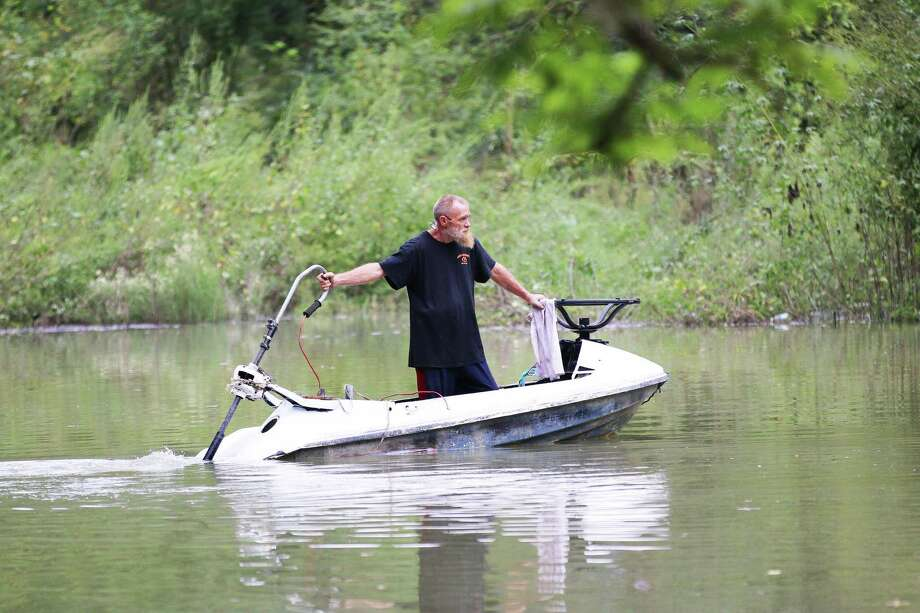 This Dayton Lakes Estates resident has adapted to the flooded road with his cleverly-created water craft to get in and out of the community. Residents say they have only had a few days since last August where they could drive in or out of their subdivision because of the flooded road. Photo: David Taylor / Staff Photo