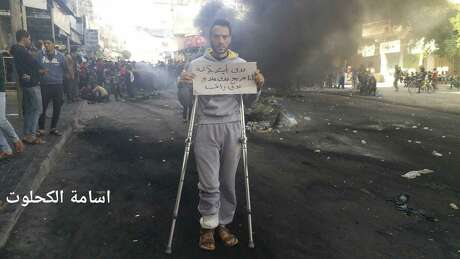 """This photo provided by Palestinian journalist Osama al-Kahlout shows a protestor holding a sign that reads in Arabic, """"I want to live in dignity; I'm wounded and need treatment and a salary,"""" during a protest in Deir al Balah, central Gaza Strip, on Friday, March 15, 2019. On the left side is Al-Kahlout's name in Arabic. Al-Kahlout was detained the next day as he went live on Facebook during another protest. He said police smashed furniture, seized his belongings and beat him on the way to the police station. Hamas is facing the biggest demonstrations yet against its 12-year rule of the Gaza Strip, with hundreds of Palestinians taking to the streets in recent days to protest the dire living conditions in the blockaded territory."""