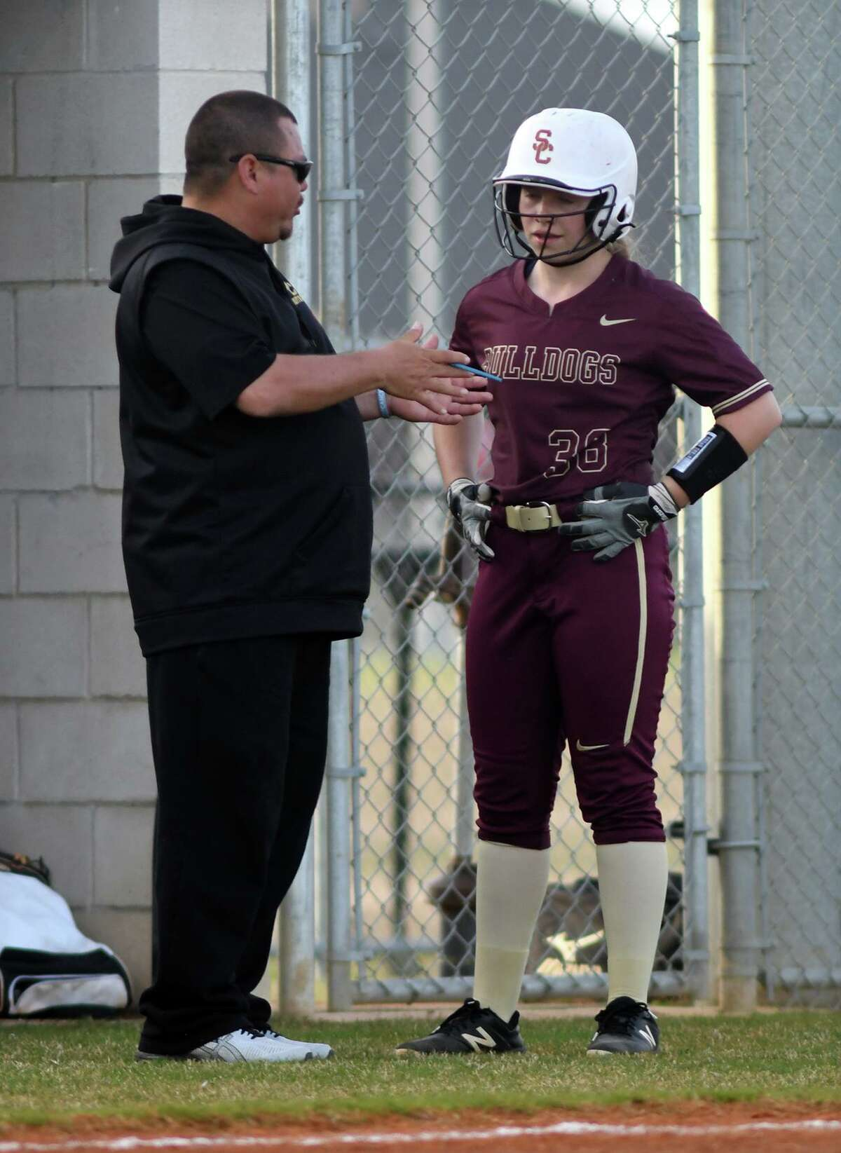Summer Creek Head Softball Coach Gabe Castillo, left, chats with sophomore first baseman Zoe Butts before her at bat against Katy Paetow during their matchup in the Katy ISD Invitational Varsity Softball Tournament at Paetow High School on Feb.14, 2019.