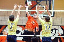 Edwardsville junior Daniel Pauk, middle, goes for a kill between two Belleville Althoff players during Thursday's season opener at Lucco-Jackson Gymnasium.