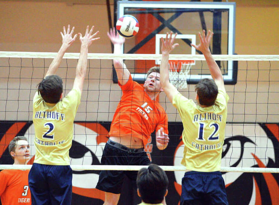 Edwardsville junior Daniel Pauk, middle, goes for a kill between two Belleville Althoff players during Thursday's season opener at Lucco-Jackson Gymnasium. Photo: Scott Marion/Intelligencer