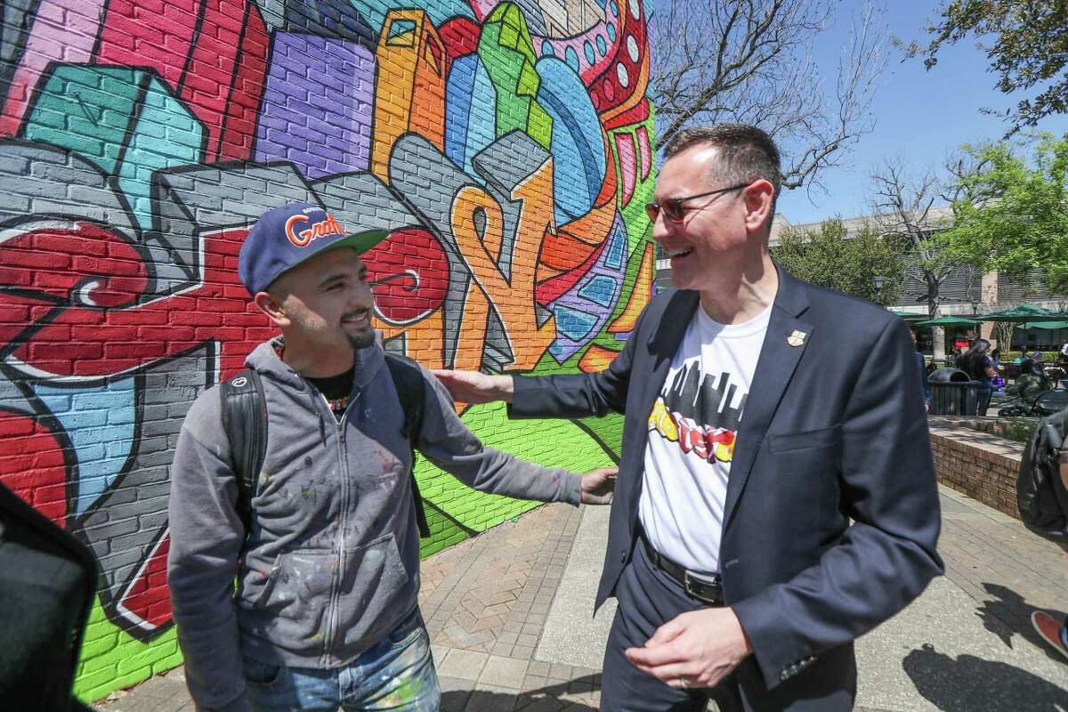 University of St. Thomas President Richard Ludwick talks with well-known graffiti artist Mario Figueroa, Jr., who goes by the moniker Gonzo247 during the unveiling of the university's first on-campus mural Thursday, March 21, 2019, in Houston. The large mural depicts St. Thomas Aquinas, the Italian Catholic priest who inspired the university's name.