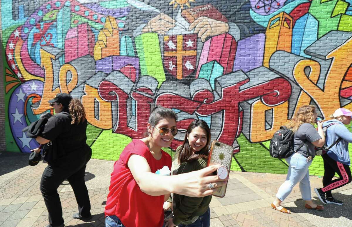 University of St. Thomas students Raiza Torres, left, and Heidi Chang attempt to take a photo in front of Gonzo247's first on-campus mural Thursday, March 21, 2019, in Houston. The large mural was painted by well-known graffiti artist Mario Figueroa, Jr., who goes by the moniker Gonzo247, depicts St. Thomas Aquinas, the Italian Catholic priest who inspired the university's name.