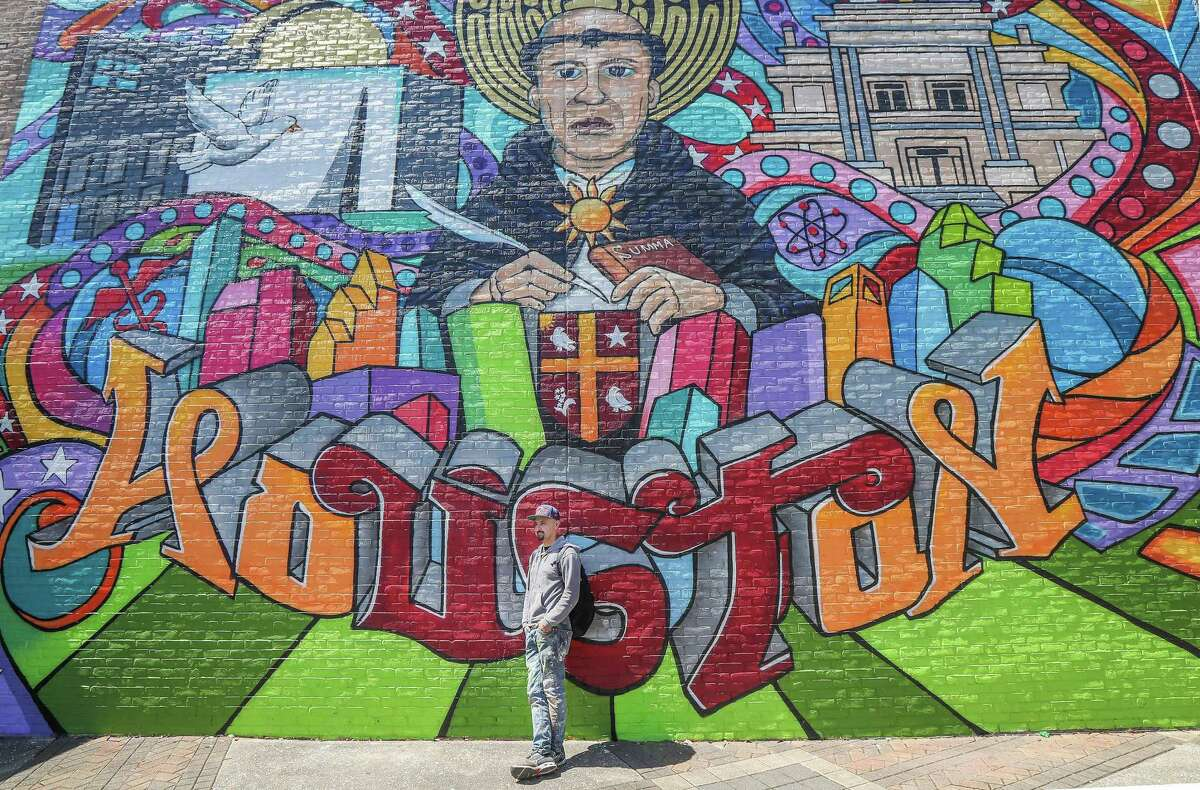 Mario Figueroa Jr., who goes by the moniker Gonzo247 poses for photos in front of his latest mural on the University of St. Thomas campus Thursday, March 21, 2019, in Houston.
