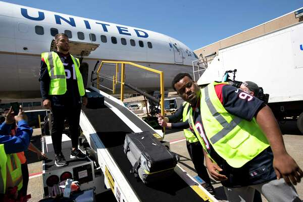 Houston Texans linebacker Dylan Cole (51) and defensive end Carlos Watkins (91) help load baggage aboard an United aircraft as the Texans players, cheerleaders and Toro visited with passengers and helped with some operations at George Bush Intercontinental Airport on Thursday, March 21, 2019, in Houston.