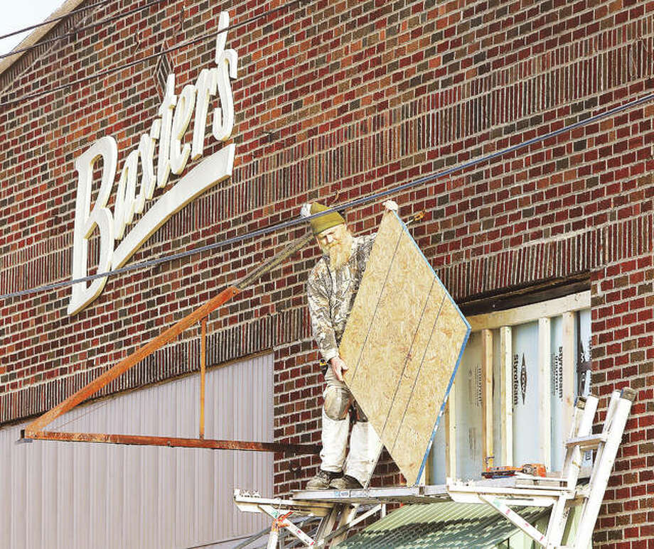 A worker puts up a particle board backing before installing siding on a portion of the front of Baxter's Distributing Co., 912 E. East Broadway, in Alton Thursday. The facelift work will replace awnings that are on the front of the party supply store. The largest of those awings blew down in a wind storm several weeks ago.