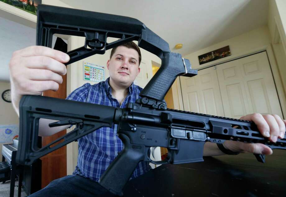 In this March 15, 2019 photo, Ryan Liskey displays a bump stock on top of his AR-15 at his home in Harrisonburg, Va. The ban on bump stocks is just a few days away and owners of the devices like Liskey are trying to figure out what to do. (AP Photo/Steve Helber) Photo: Steve Helber / Copyright 2019 The Associated Press. All rights reserved