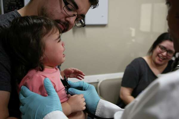 Nick Elizondo, left, holds his one-year-old daughter, Lyla, as she is examined by Harris County physician assistant Felicia Boutte at Harris County Public Health's mobile clinic Thursday, March 21, 2019, in Deer Park, Texas. The clinic was setup in response to the aftermath of the ITC petrochemical fire.
