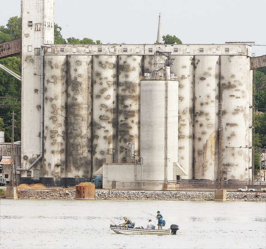 A group of anglers try their luck in the hot sun on the Mississippi River across from the ConAgra Mill in Alton.