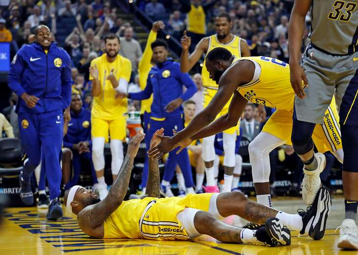 Golden State Warriors' DeMarcus Cousins is helped up by Draymond Green after scoring while being fouled in 1st quarter against Indiana Pacers during NBA game at Oracle Arena in Oakland, Calif., on Thursday, March 21, 2019.