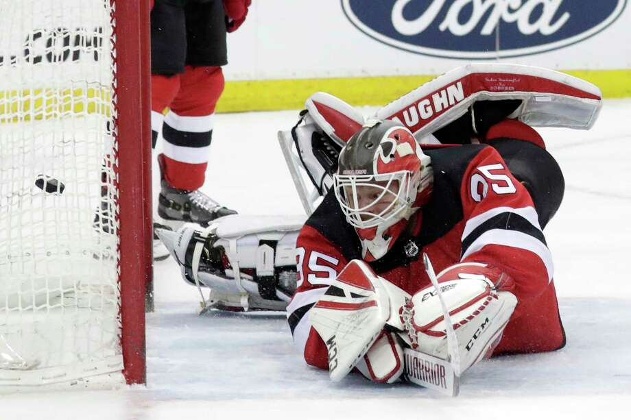 56f3c705b4e New Jersey Devils goaltender Cory Schneider looks back as a shot by Boston  Bruins center Patrice