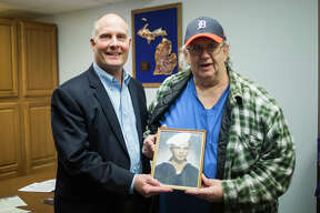 Sanford resident Dennis Webster, right, and U.S. Rep. John Moolenaar, left, pose for a photo after Dennis was presented with the National Defense Service Medal and the Sharpshooter Badge with Rifle Bar on Thursday, March 21, 2019 in Moolenaar's office in Midland. Webster was also presented with honors on behalf of his father, David Webster, who served in the Army and the Navy during World War II. (Katy Kildee/kkildee@mdn.net)