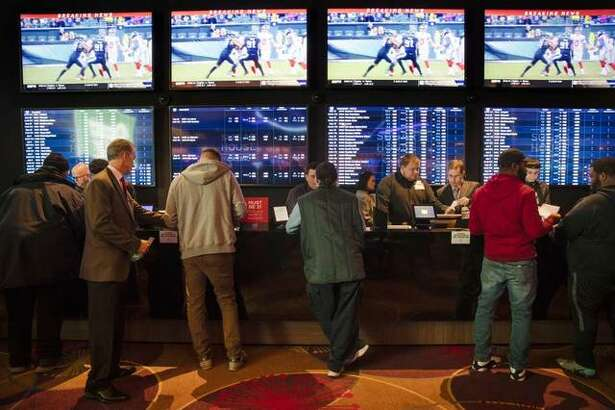 FILE - In this Thursday, Dec. 13, 2018, file photo, gamblers place bets in the temporary sports betting area at the SugarHouse Casino in Philadelphia. About six in 10 Americans want betting on professional sports events to be legal in their state, but fewer feel that way about college athletics, according to a new poll conducted by The Associated Press-NORC Center for Public Affairs Research released Wednesday, March 20, 2019. The poll finds 42 percent favor legal betting on college sports
