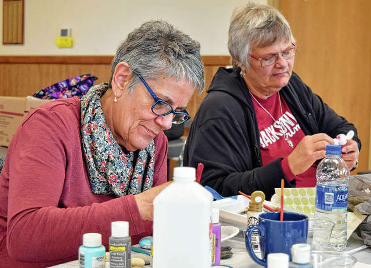 Sue Lee of Woodson and Kathy Turner of Jacksonville follow instructor Julie Kennedy's directions as they paint rocks Thursday as part of a Jacksonville Area Senior Center craft class at the Community Park Center.