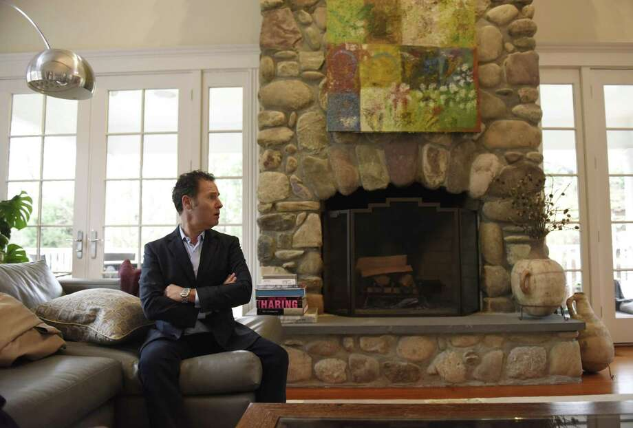 Architect Richard Granoff sits in the living room of his home on Witherell Drive in Greenwich. The neo shingle-style home features oversized windows, a three-car garage, drop-down projector and screen, pool and hot tub, and a large outdoor space with a variety of trees and a ridge of rocks, which is the namesake of nearby Rock Ridge Road. Photo: Tyler Sizemore / Hearst Connecticut Media / Greenwich Time