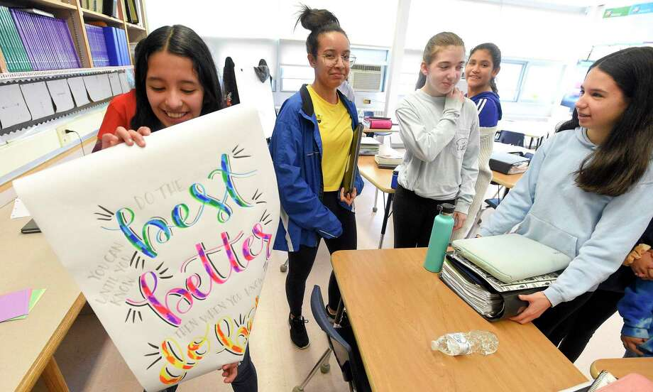 "Seventh-grader Stephanie Salinas, left, holds a quote she won in class following a team building classroom exercise ""Would you Rather"" in Alisha Barry's AVID class at Western Middle School in Greenwich, Connecticut on March 8, 2019. Photo: Matthew Brown / Hearst Connecticut Media / Stamford Advocate"