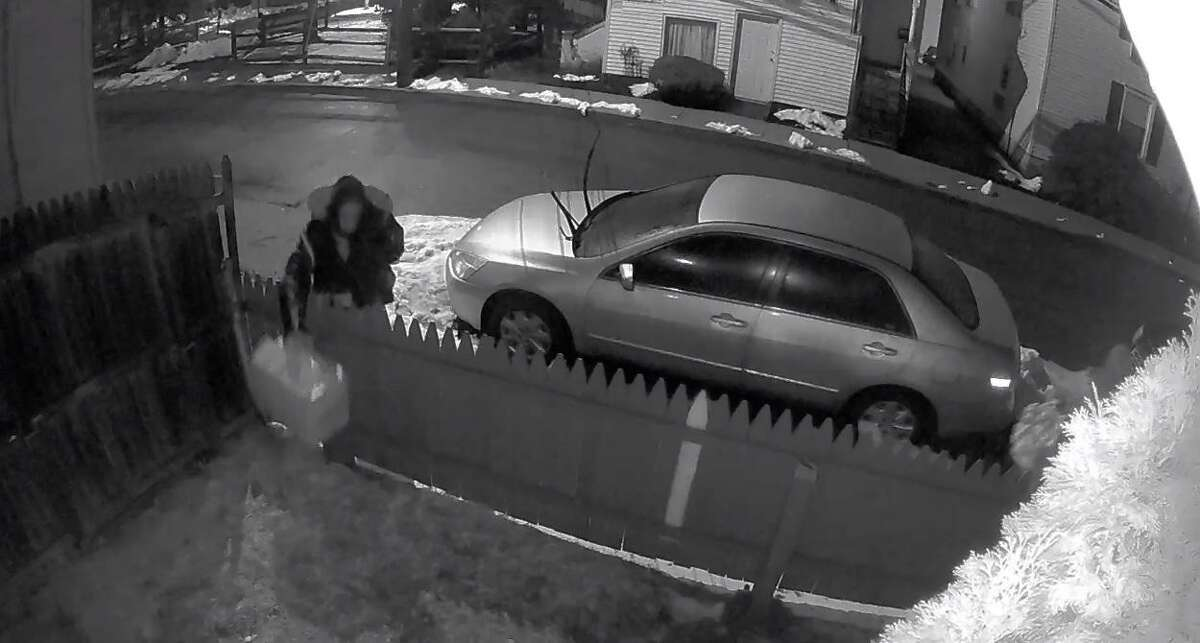 Screenshot from a video posted by Westport police showing a suspect dropping a box at a Westport home.