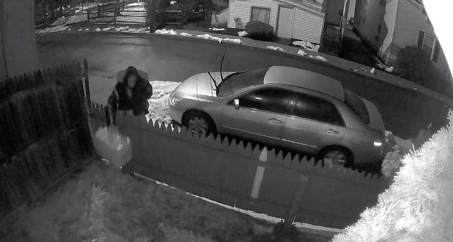 Screenshot from a video posted by Westport police showing a suspect dropping a box at a Westport home. Photo: Westport Police