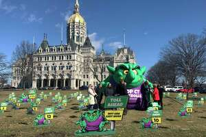 "Opponents of highway tolls in Connecticut pose in front of an inflatable ""Toll Troll"", Tuesday, March 19, 2019, outside the Connecticut State Capitol in Hartford, Conn. The conservative Yankee Institute for Public Policy organized the protest ahead of a planned committee vote on tolls. (AP Photo/Susan Haigh)"