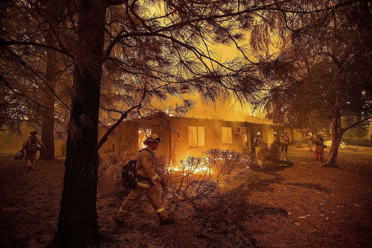 FILE - In this Nov. 9, 2018, file photo firefighters work to keep flames from spreading through the Shadowbrook apartment complex as a wildfire burns through Paradise, Calif. California is calling in the National Guard for the first time to help protect communities from wildfires like the one that destroyed much of the city of Paradise last fall. Starting in April 2019, 110 California National Guard troops will receive 11 days of training in using shovels, rakes and chain saws to thin trees and brush. (AP Photo/Noah Berger, File)