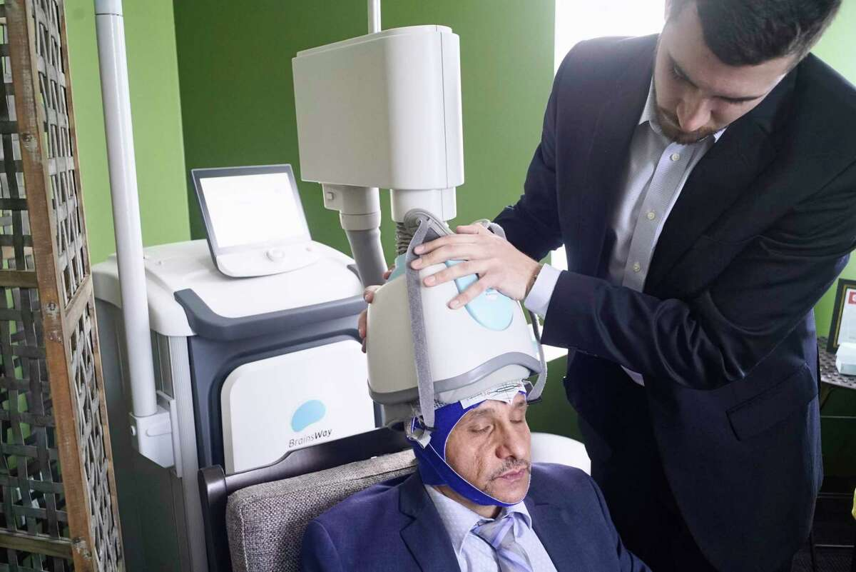 Rocco Pezzulo, left, director of operations, sits for a demonstration on how the helmet is placed on the patient's head by John Seymour, a TMS specialist, for a Transcranial Magnetic Stimulation therapy session at Pinnacle Behavioral Health on Tuesday, March 19, 2019, in Albany, N.Y. Pezzulo said that he is also getting daily TMS therapy to help him think clearer, to be more focused and for what he calls peak performance. (Paul Buckowski/Times Union)