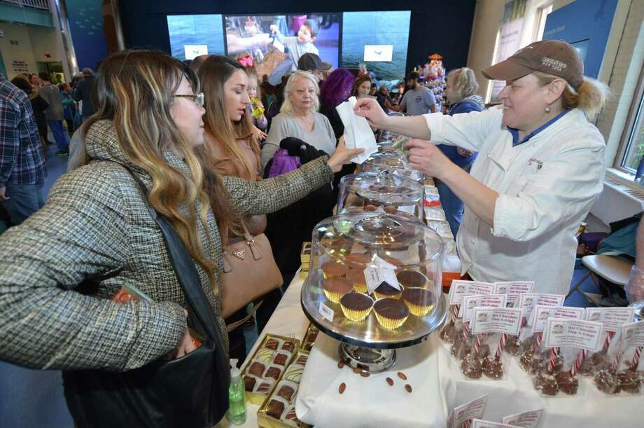 Patrons purchase sweets at the 2017 installment of the annual Chocolate Expo at Maritime Aquarium in Norwalk, Conn. Confectionery sweets have drawn early interest among entrepreneurs under Connecticut's new cottage food law that allows for commercial sale of some foods produced in home kitchens, with overall uptake under the law still slow in the first six months of the new rules. Photo: Alex Von Kleydorff / Hearst Connecticut Media / Connecticut Post