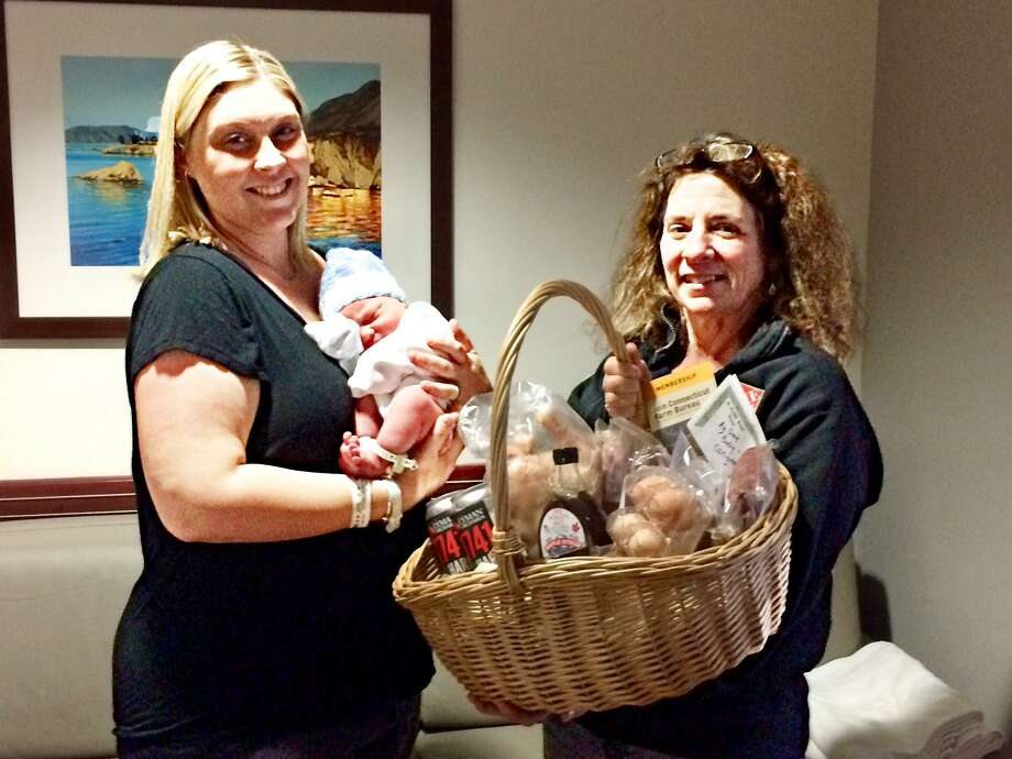 Andi Hills, right, Middlesex County Farm Bureau Women's Leadership Chair presents a basket of agricultural products from local farmers to East Haddam residents Ashley Smith, left and son Maddox, the 2019 Ag Day Baby. Photo: Contributed Photo