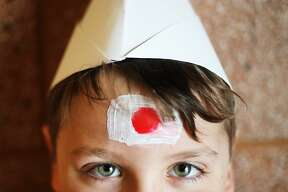 Benjamin Angel, 9, wears a hat he made, inspired by traditional hats worn in Kyrgyzstan, and a Japanese flag on his forehead during the Passport to the World international fair held at SVSU on Friday, March 22, 2019. Fourth graders from Chestnut Hill and Bangor Lincoln schools attended the event, which celebrated cultures from around the world. (Katy Kildee/kkildee@mdn.net)